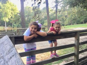 Girls playing on a wooden fence at Gillis Hill Farm in Fayetteville, North Carolina.