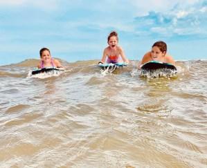 Girls riding boogie boards at a Texas beach.