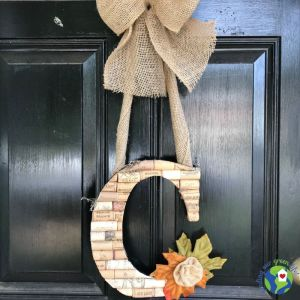 letter C made with wine corks hanging on door