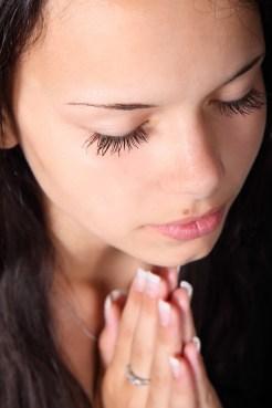 woman praying eyes closed