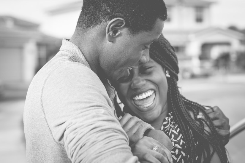 african american couple laughing and hugging
