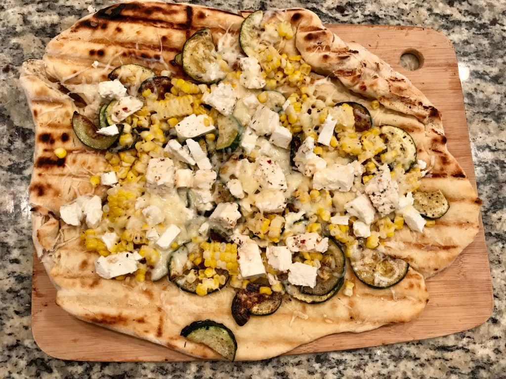 Grilled Pizza with Zucchini, Corn, & Marinated Feta | This grilled zucchini pizza is perfect for summer, delicious and easy. Grilled corn and salty marinated feta add to the flavors, along with an easy chewy homemade pizza crust. Perfect grilling recipe. #grilling #grilledpizza #summerrecipes