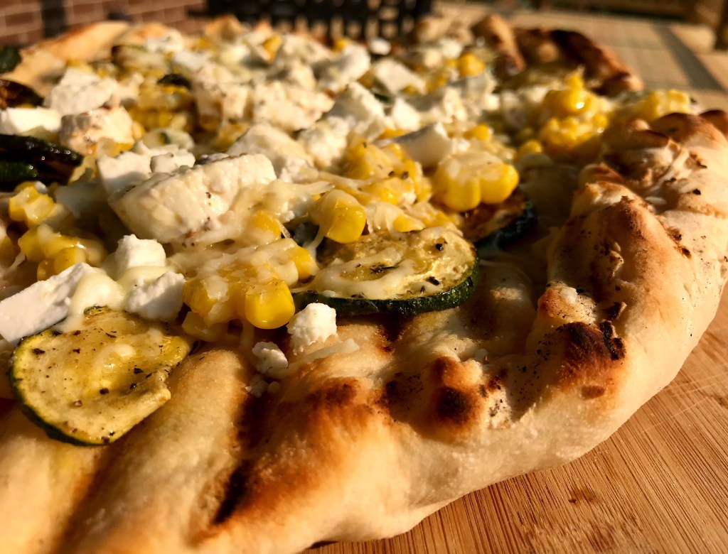 Grilled pizza dough with zucchini, corn, and marinated feta