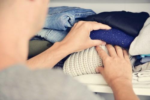 closeup of a young caucasian man arranging the closet