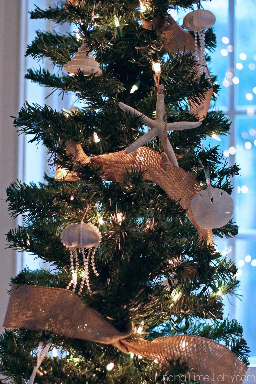 Coastal Christmas Keeping Room with elegant fireplace mantle, seashell Christmas trees, starfish garland and seashell ornaments