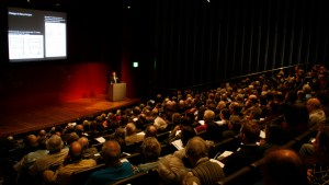A speaker at a podium in the BP lecture theatre at the British Museum talking to a conference crowd
