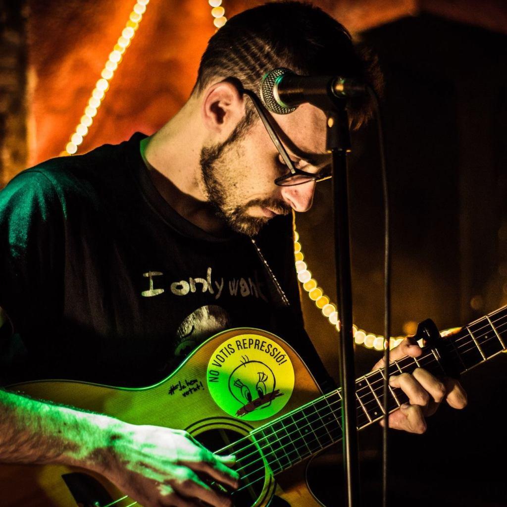 Oscar Martínez frente a un micrófono sujetando su guitarra