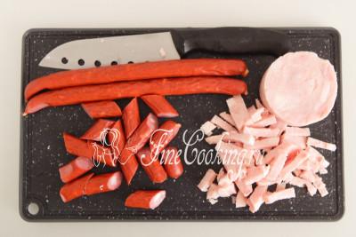 Берем по 200 граммов копченой колбасы и ветчины, и нарезаем произвольными ломтиками