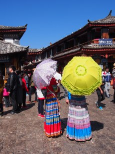 Women posing for photos in traditional dress in Lijiang Market Square.
