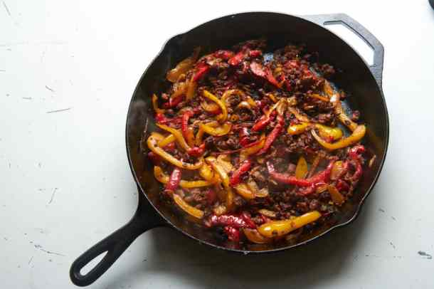 Cast iron skillet with red and yellow bell peppers, onions, and chorizo