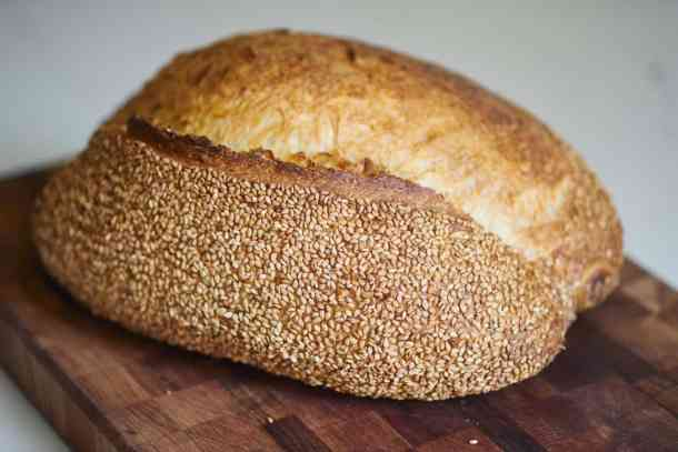 A loaf of Italian bread with sesame seeds sits on a wooden cutting board.