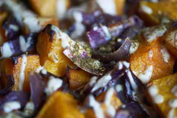 Closeup of roasted butternut squash with red onion, tahini sauce and za'atar spice based on a recipe from the cookbook Jerusalem by Ottolenghi and Tamimi displayed on a white plate.
