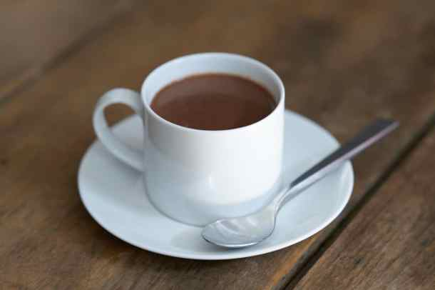 French-style hot chocolate in a white coffee cup on a white saucer with a silver spoon. The saucer sits on a wooden surface.