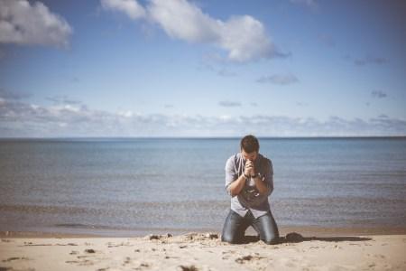 바닷가에서 무릎 꿇고 간절히 기도