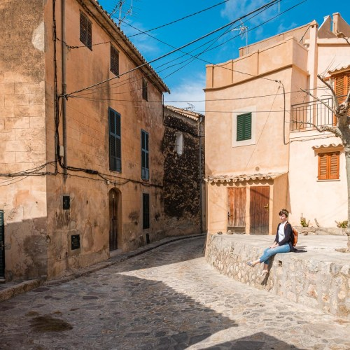 A girl sits in the sun on a wall in a Majorcan village