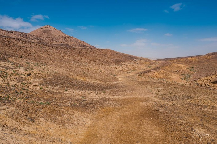 A dusty path through the Makhtesh Ramon with blue sky