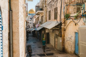 A girl walks through a narrow alley in the old town of Jerusalem