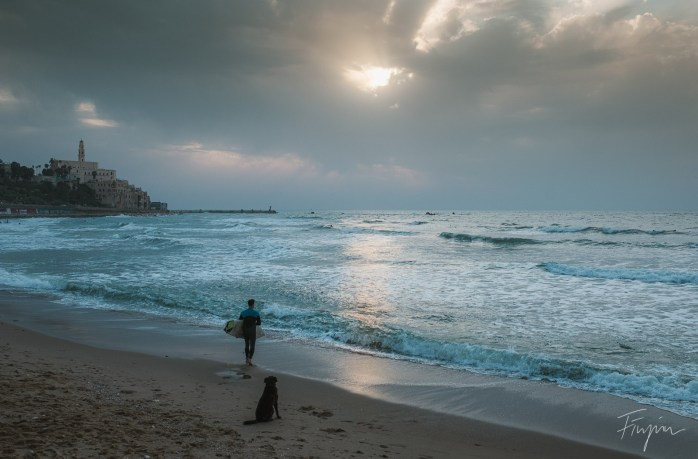 A man is about to go into the water to surf at sunset