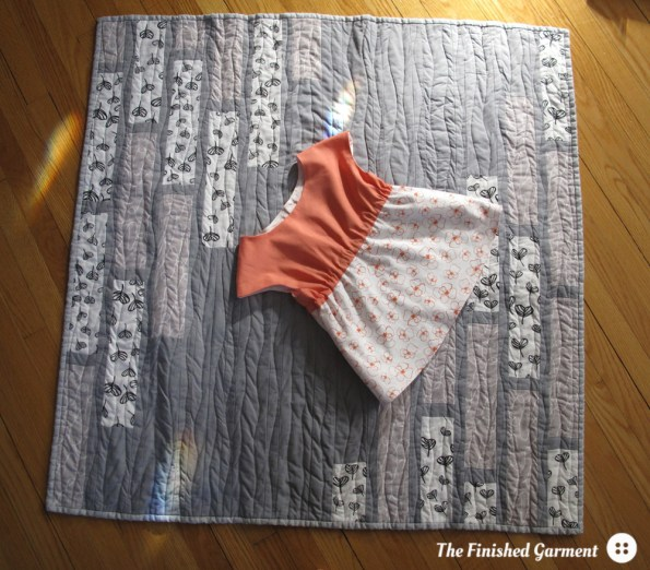 A monochromatic baby quilt and tunic sewn by The Finished Garment.