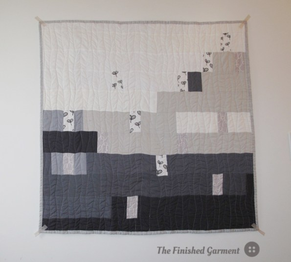A monochromatic baby quilt sewn by The Finished Garment.
