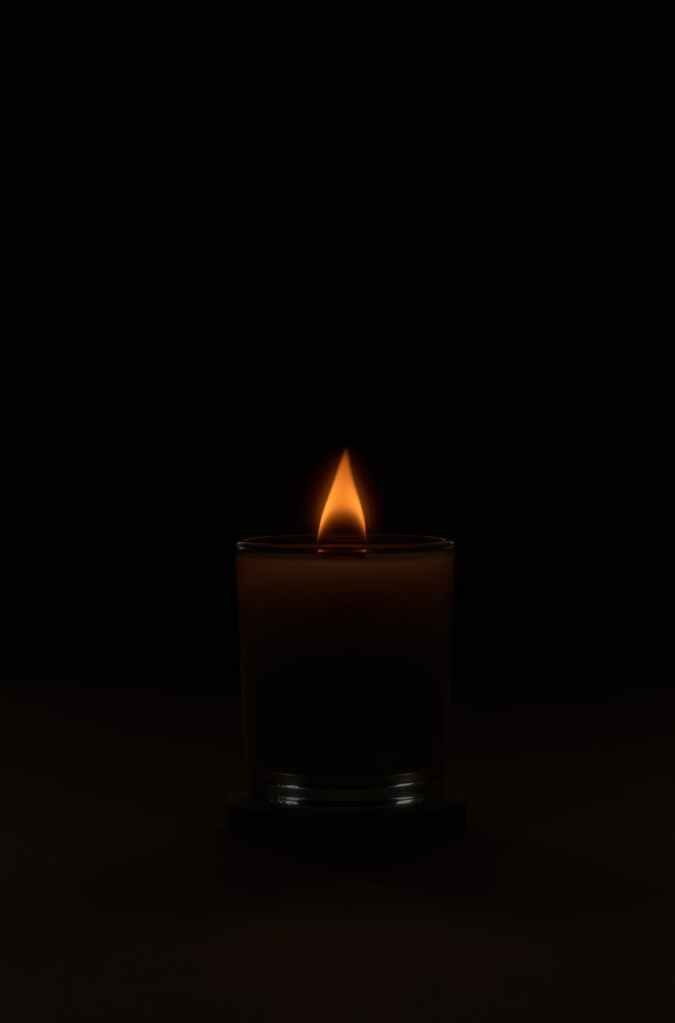 flaming candle in dark obscure studio