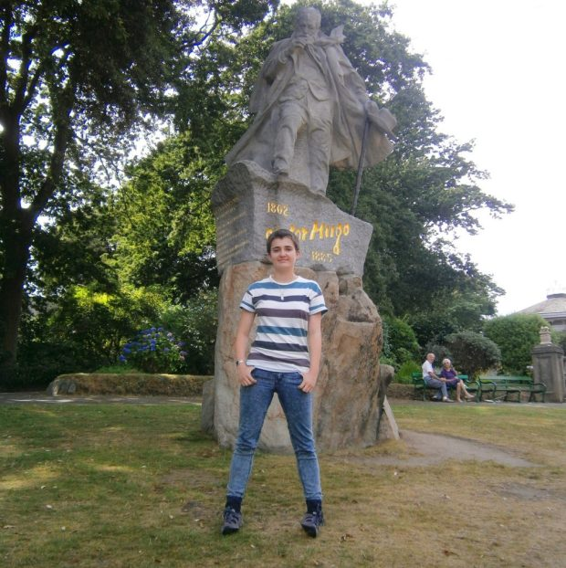 Photo of a person with short dark hair wearing a stripy t-shirt and jeans, standing proudly in front of a statue of Victor Hugo.