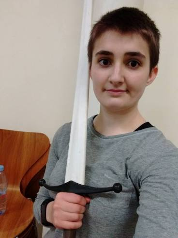 A selfie of me, holding a practice longsword with a white nylon blade. I'm wearing a grey long-sleeved top and I have short dark hair.