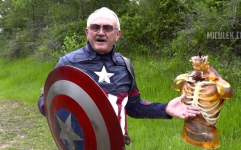 Un señor mayor disfrazado de Capitán América lanzándole su escudo a un dummie de gel balístico