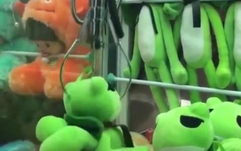 Neo jugando a la máquina de pillar peluches
