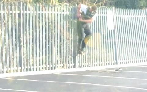 Un policía se queda miserablemente enganchado en una valla