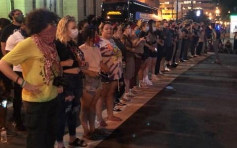 Un montón de mujeres blancas hacen una fila delante de los manifestantes negros para protegerles de la policía