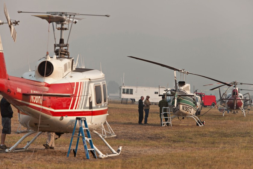 With the FAA control tower in the background, crews prepare helicopters at the Hopps Helibase for the day's missions on large fires around Colville, WA.