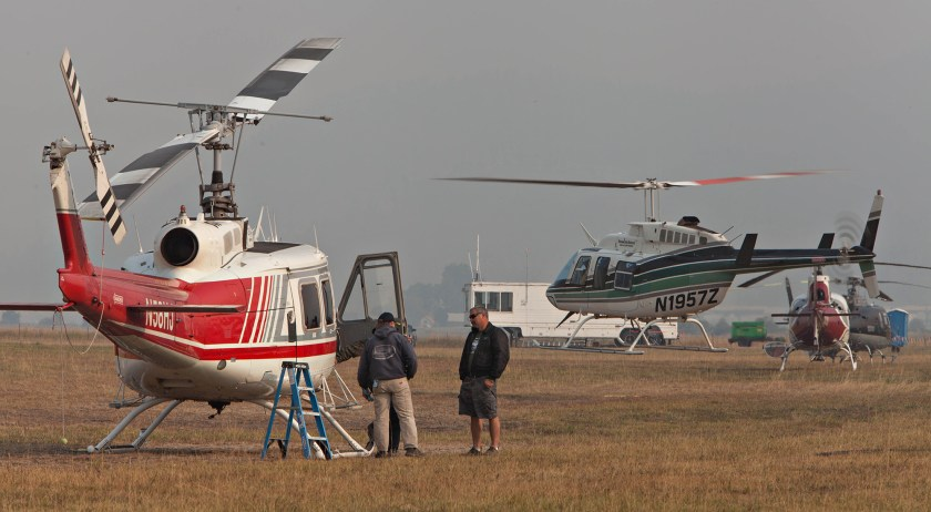 With the FAA control tower in the background and a Bell 205 A1 ++ in the foreground, a Bell 206 L4 carrying members of Swan Valley Helitack from the Caribou-Targhee National Forest, take off for a mission on the Carpenter Road Fire.