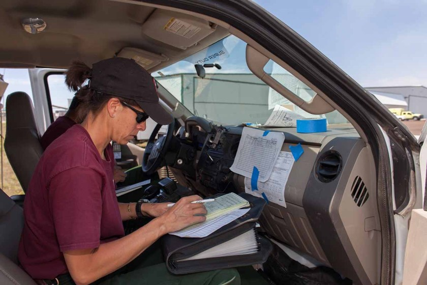 Challenged by a pretty good breeze and lack of decent writing surface Angie Tom of Twin Falls Helitack runs the deck operations from the passenger seat of Durango Helitack's vehicle.