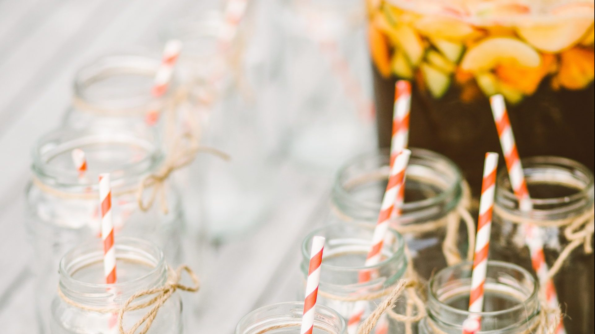 Housewarming punch bowl filled with fruit with mason jars and paper straws