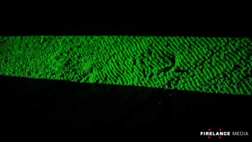 Green laser highlighting a footprint during night tracking