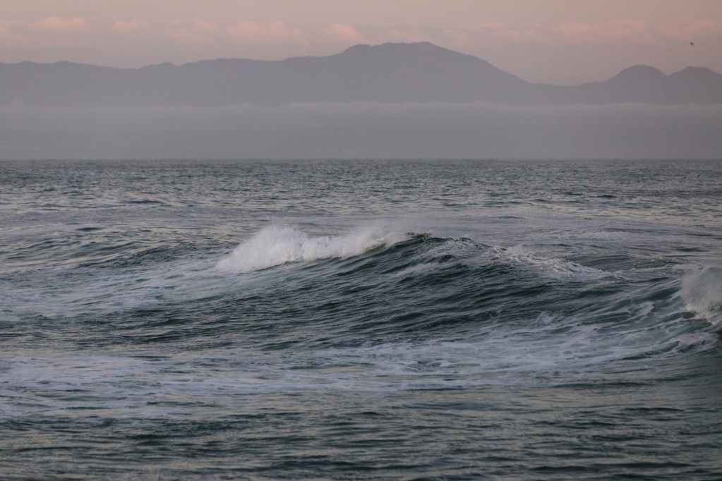 foamy sea waves against high mountains on cloudy weather