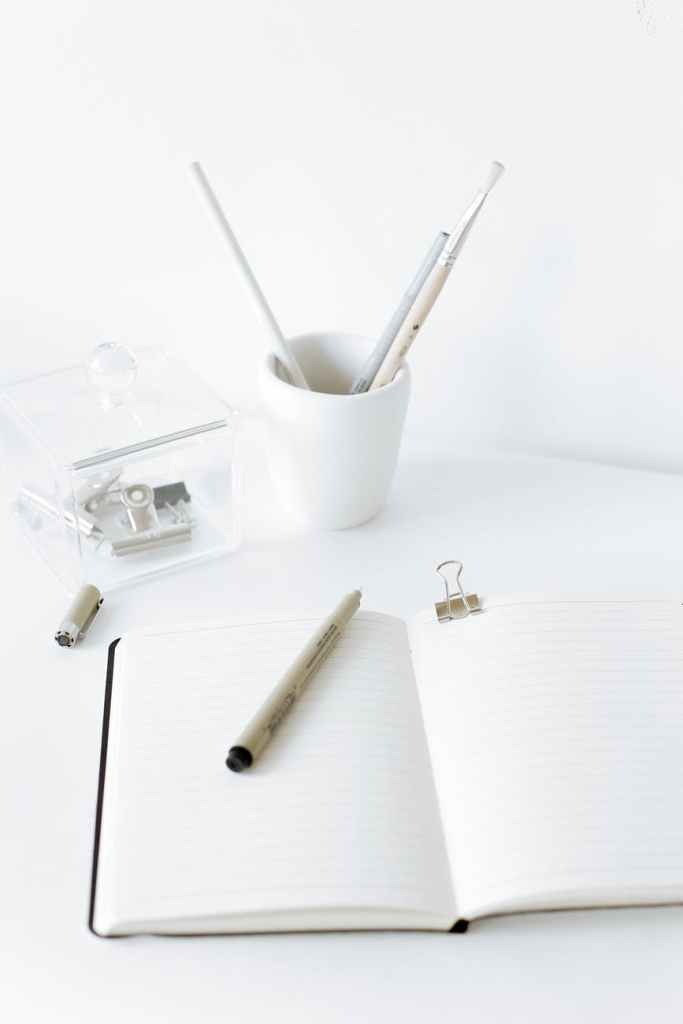 opened notebook with pen on white desk