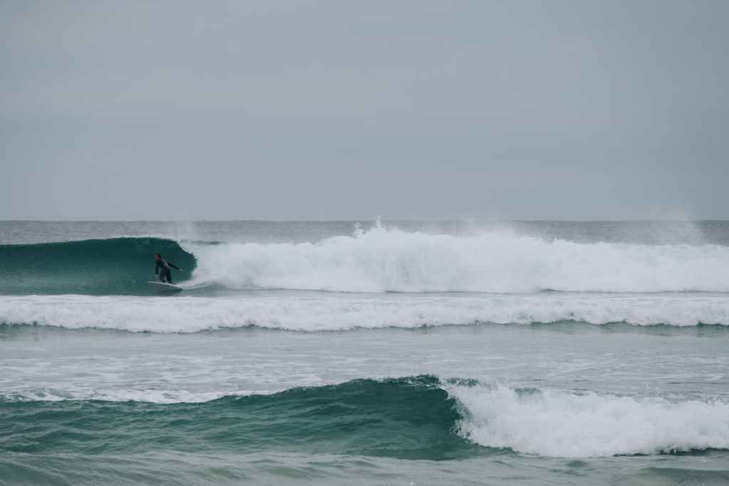 surfer riding surfboard on wavy ocean in stormy day