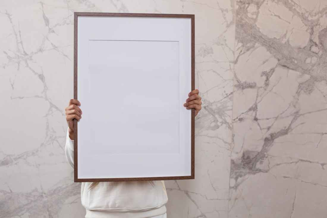 person showing large blank frame near wall with patterns