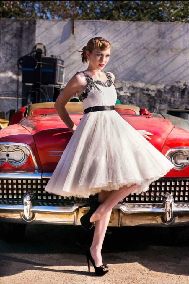 me in 50s style dress modelling in front of a red convertible 50s car