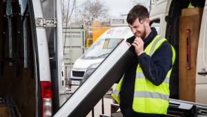 worker looking at guttering as an example of business photography