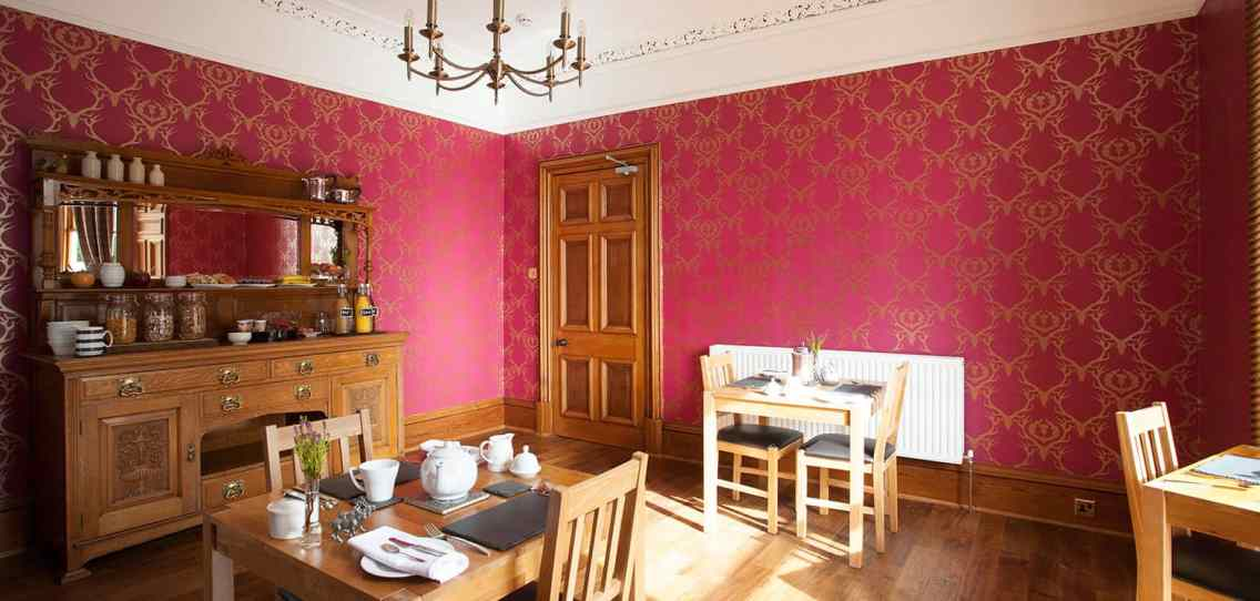 Dining room laid out with tables set up for two people with wooden floors and red patterned wallpaper