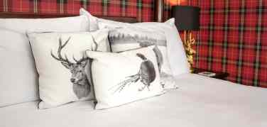 Cushions with hand drawn pictures of animals clustered on a four poster bed with tartan wall paper in the background