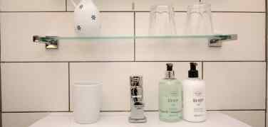Scottish Fine Soaps sea kelp range of toiletries on display on a white sink under a glass shelf