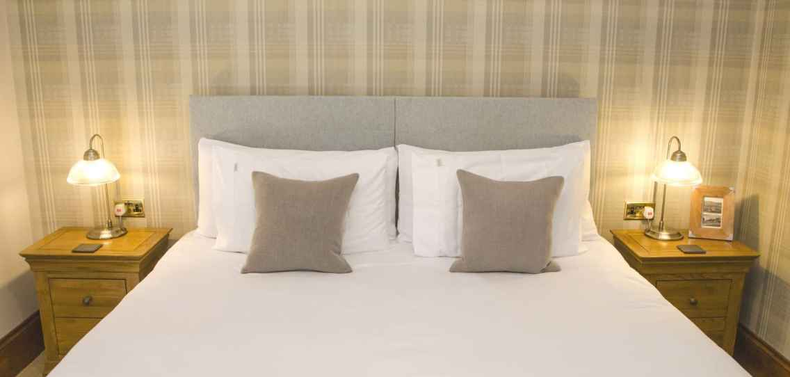King size bed made up with white bedlinen with pale plaid wall paper in the background and oak bedside tables