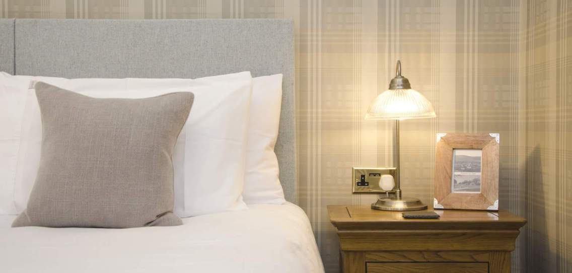 white pillows on a bed next to an oak bedside table with table lamp in the Harris room at Firhall Bed & Breakfast