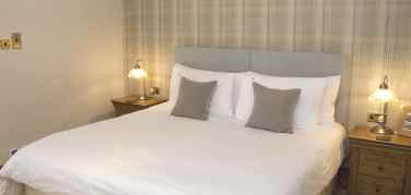 kingsize bed made up with white bed linen and off white cushions next to bedside tables with lamps on