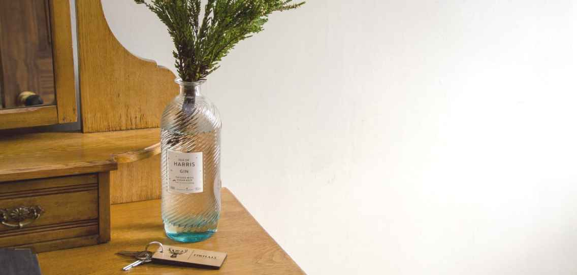 Harris Gin bottle being used as a vase for local sprigs of heather at Firhall Highland B&B