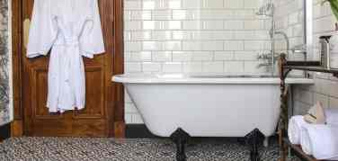 Large white bath with claw feet in bathroom decorated with black and white floor tiles and oak door